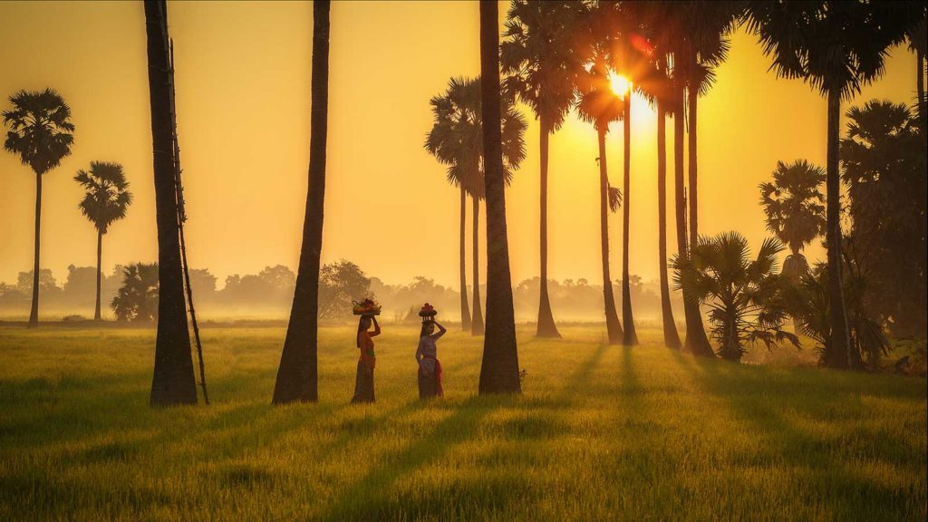Two Balinese women carrying offerings at sunrise